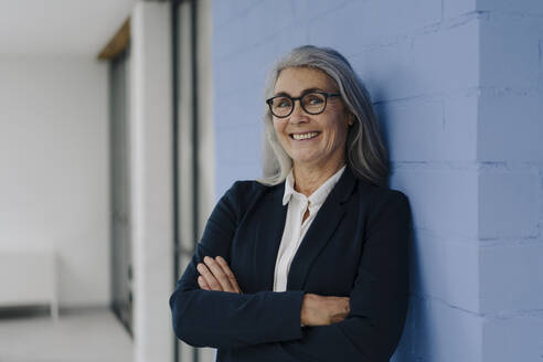 Portrait of smiling grey-haired businesswoman standing at a blue wall - GUSF03357