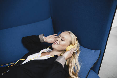 Smiling young businesswoman lying on couch listening to music with headphones - GUSF03387