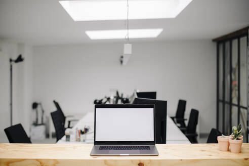 Laptop in conference room in loft office - GUSF03423