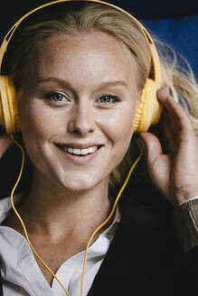 Portrait of a smiling young businesswoman listening to music with headphones - GUSF03438