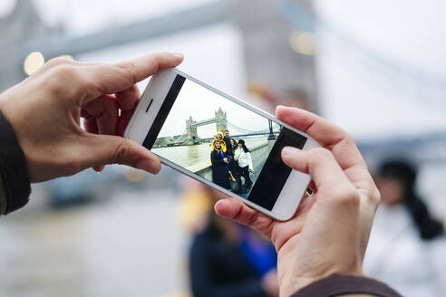 Group of tourists taking smartphone pictures, with  London Bridge in background - DGOF00498