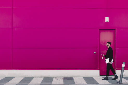 Businessman with smartphone and documents walking along a pink wall - ERRF02781