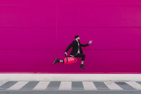 Young man jumping with travelling bag in front of a pink wall - ERRF02793