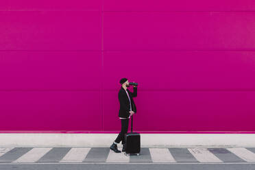 Young man with trolley walking along a pink wall, drinking from a reusable cup - ERRF02796