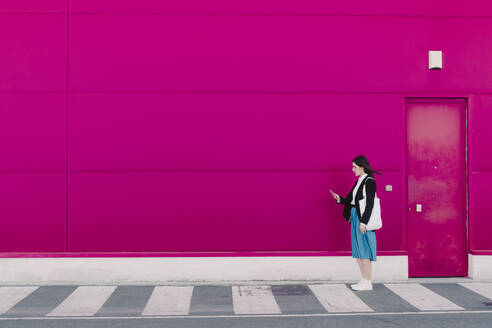 Young woman holding smartphone and waiting at a pink wall - ERRF02799