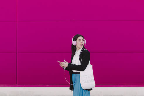 Young woman walking along pink wall, using smartphone and listening to music, organic shopping bag and looking back - ERRF02802