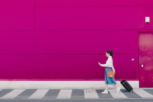 Young woman using smartphone and walking with trolley along a pink wall - ERRF02808