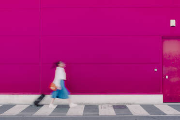 Young woman with smartphone walking with trolley along a pink wall, blurred - ERRF02811