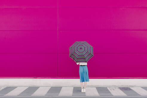 Rear view of young woman with umbrella standing in front of a pink wall - ERRF02814