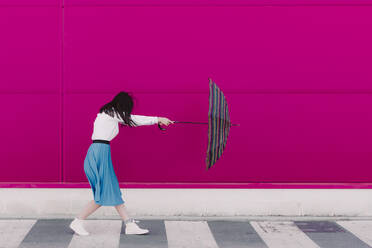 Young woman holding umbrella in front of a pink wall - ERRF02817