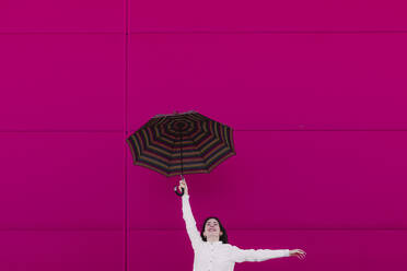 Young woman jumping with umbrella in front of a pink wall - ERRF02820
