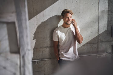 Young man wearing t-shirt talking on the phone at concrete wall - PNEF02383
