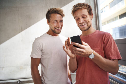 Two happy young men sharing smartphone - PNEF02386