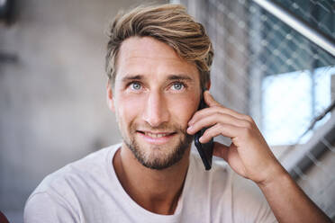 Portrait of young man wearing t-shirt talking on the phone - PNEF02401