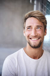 Portrait of smiling young man wearing white t-shirt - PNEF02404