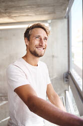 Portrait of smiling young man wearing white t-shirt looking out of window - PNEF02410