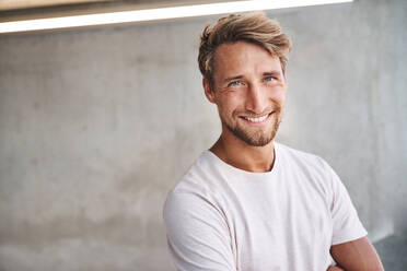 Portrait of smiling young man wearing white t-shirt - PNEF02413