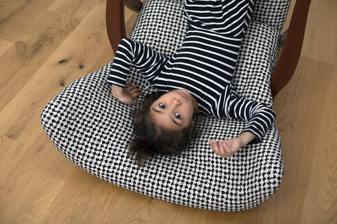 Portrait of little girl lying upside on armchair - PSTF00637