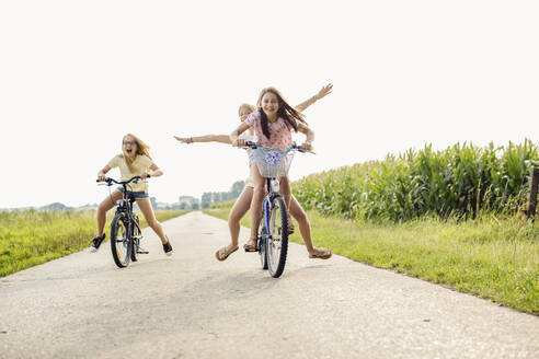 Happy girls riding bicycle on a country lane - SODF00627