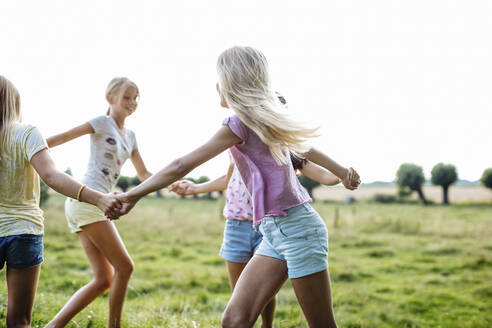 Happy girls dancing on a field together - SODF00633