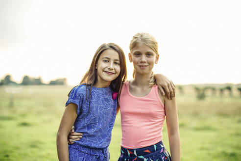 Portrait of two smiling girls embracing on a field - SODF00681
