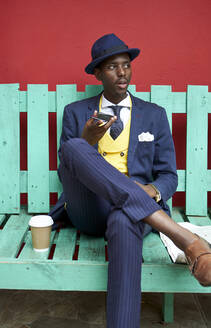 Young businessman wearing old-fashioned suit and hat sitting on a green bench using his phone - VEGF01607