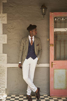 Stylish young businessmann with a beret leaning at a wall - VEGF01628
