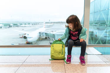 Girl with backpack sitting at the airport in front of a plane - GEMF03467