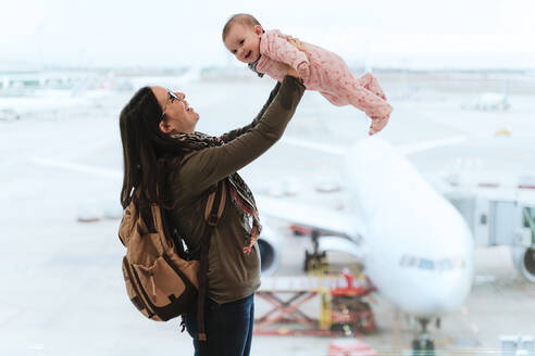 Mother with backpack playing with baby pretending to fly at the airport - GEMF03470