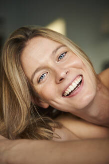 Portrait of happy blond young woman lying down - PNEF02440
