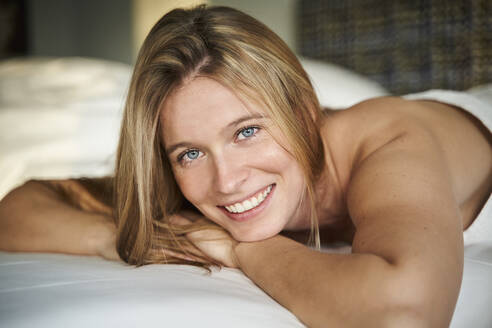 Portrait of happy blond young woman lying in bed - PNEF02443