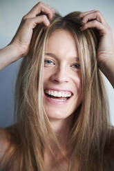 Portrait of laughing blond young woman with hands in hair - PNEF02446