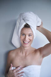 Portrait of happy young woman with her head wrapped in a towel - PNEF02449
