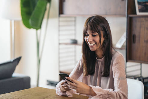 Happy young woman using cell phone at home - MPPF00545
