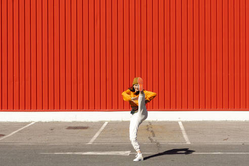 Young woman dancing in front of a red wall - ERRF02828