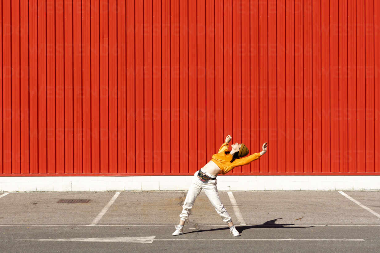 Young woman dancing in front of a red wall - ERRF02831 - Eloisa Ramos/Westend61