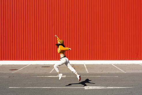 Young woman dancing in front of a red wall - ERRF02834