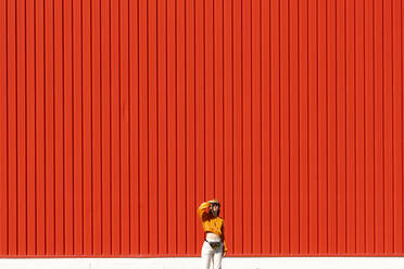 Young woman standing in front of a red wall - ERRF02837