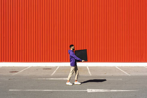 Young man carrying a box in front of a red wall - ERRF02840