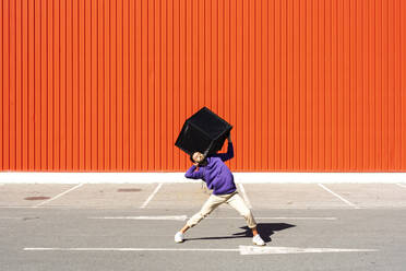 Young man carrying a box in front of a red wall - ERRF02843