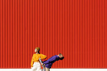 Young man and woman with a box permorming in front of a red wall - ERRF02855