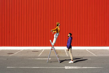 Young man and woman performing with a ladder in front of a red wall - ERRF02858