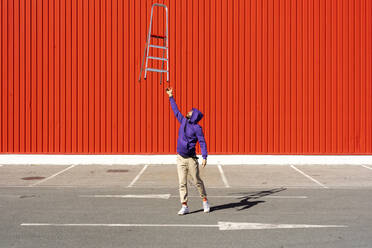 Young man balancing a ladder in front of a red wall - ERRF02861