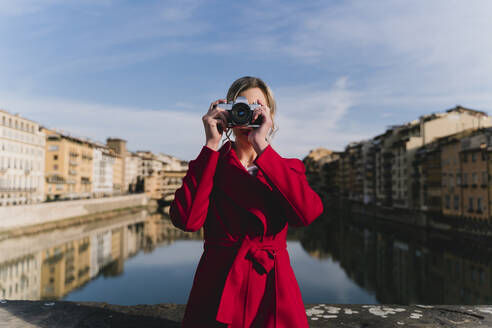 Young woman taking a picture on a bridge above river Arno, Florence, Italy - FMOF00879