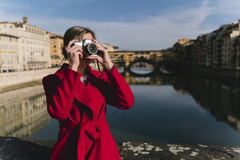Young woman taking a picture on a bridge above river Arno, Florence, Italy - FMOF00882