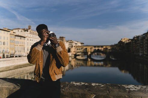 Young man taking a picture on a bridge above river Arno, Florence, Italy - FMOF00885