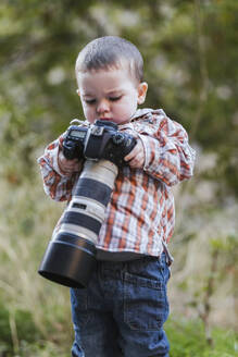 Portrait of toddler looking at digital reflex camera with big lens in nature - LJF01382