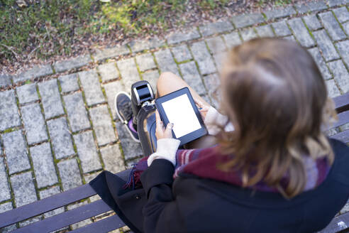Young woman with leg prosthesis sitting on a bench reading e-book - FBAF01280