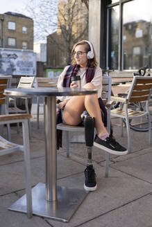 Young woman with leg prosthesis sitting in a sidewalk cafe in the city - FBAF01283