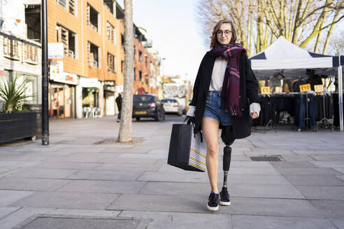 Portrait of confident young woman with leg prosthesis walking in the city - FBAF01286